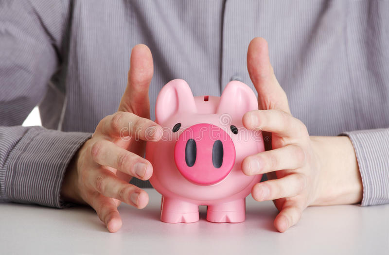 Male hands protecting piggy bank royalty free stock image