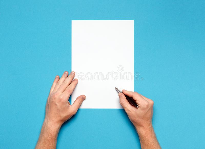 Male Hands Is Ready For Drawing With Pen, Top View On Blue Surface. Creativity Concept royalty free stock photo