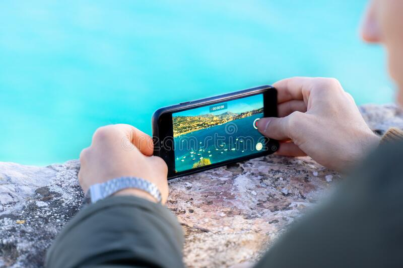Male hands recording video or making time lapse on smartphone of sailing ship yachts, sailing boats at sea harbour. sunny coast. With mountains on background royalty free stock photography