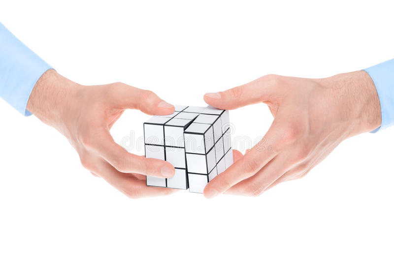 Solving a puzzle. Male hands in shirtsleeves solving a blank white twist puzzle. Isolated on white royalty free stock images
