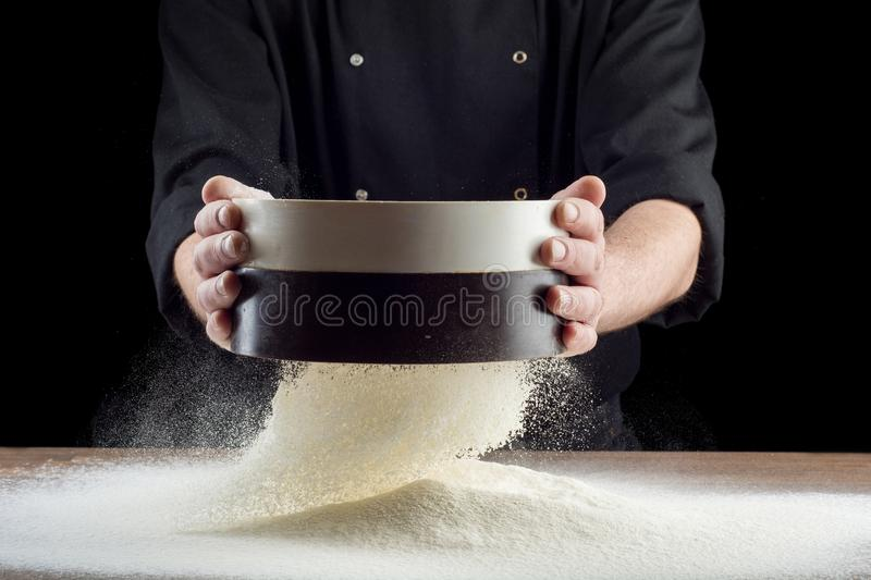 Male hands sifting flour from old sieve on old wooden kitchen table. on black background. Male hands sifting flour from old sieve on old wooden kitchen table royalty free stock photos