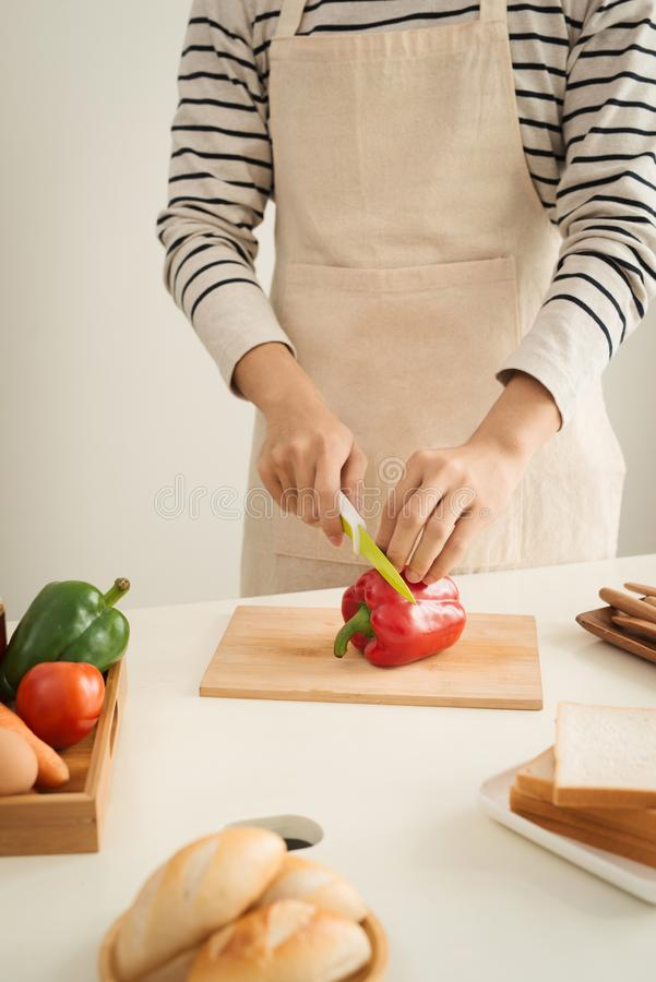 Male hands slicing fresh red bell peppers stock photo