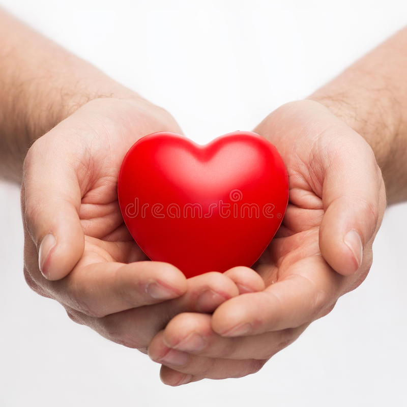 Male hands with small red heart. Health, medicine and charity concept - close up of male hands with small red heart royalty free stock images