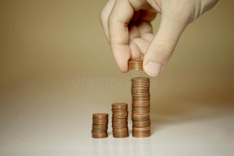 Male hands stacking money. Male hands stacking pennies and cents stock photos