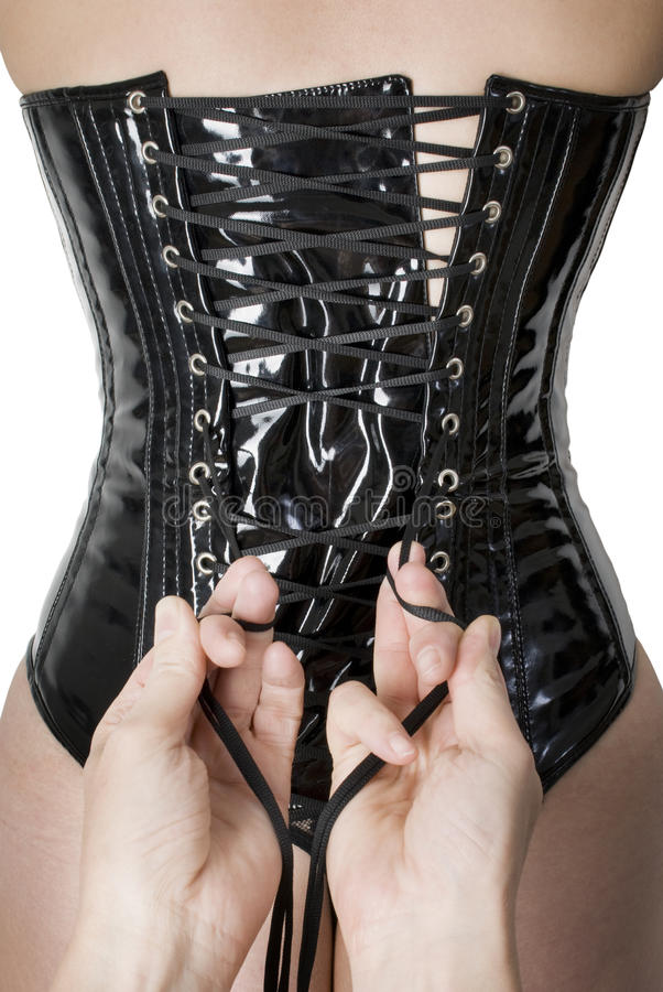 Male hands tightening up a corset. To the young woman stock image
