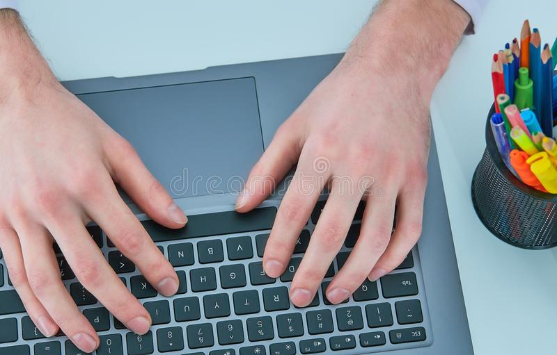 Male hands typing on laptop keyboard. Young man using laptop computer. Business working concept. stock photos