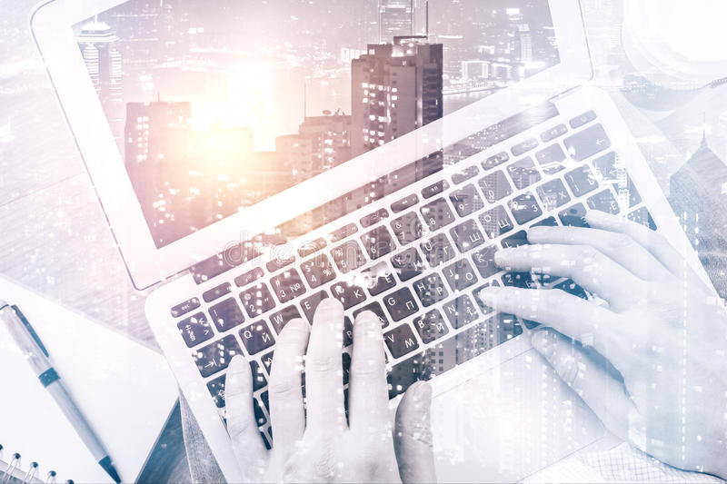 Male hands using laptop. On city background. Double exposure. Communication concept stock images
