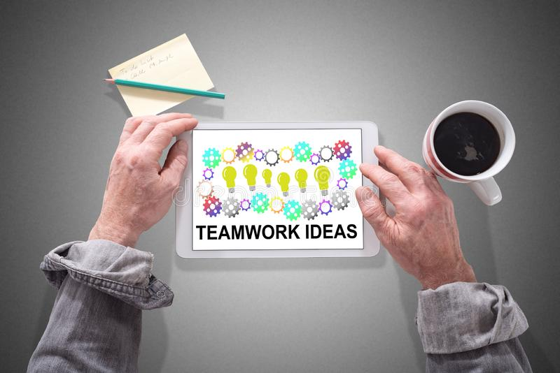 Teamwork idea concept on a tablet. Male hands using a tablet showing teamwork idea concept royalty free stock image