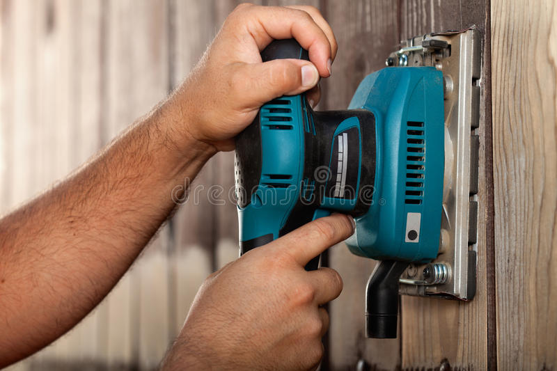 Male hands using a vibrating sander on wooden surface stock images