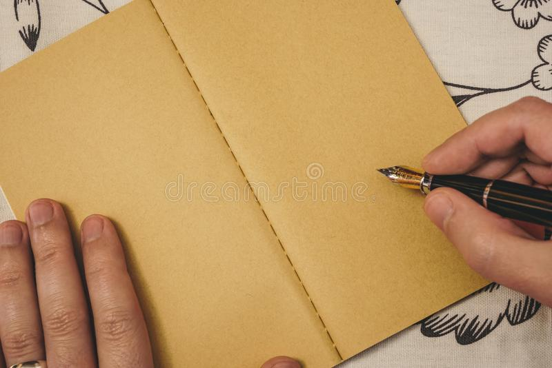 Male hands with wedding band writing with fountain pen on kraft notebook. Special event or occasion with copy space. stock photo