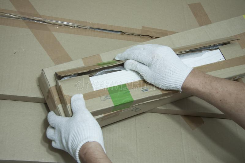 Male hands in white gloves with a knife unpack the box. Receiving mailings. Order from the store. Preparation for repair work indoors royalty free stock photo