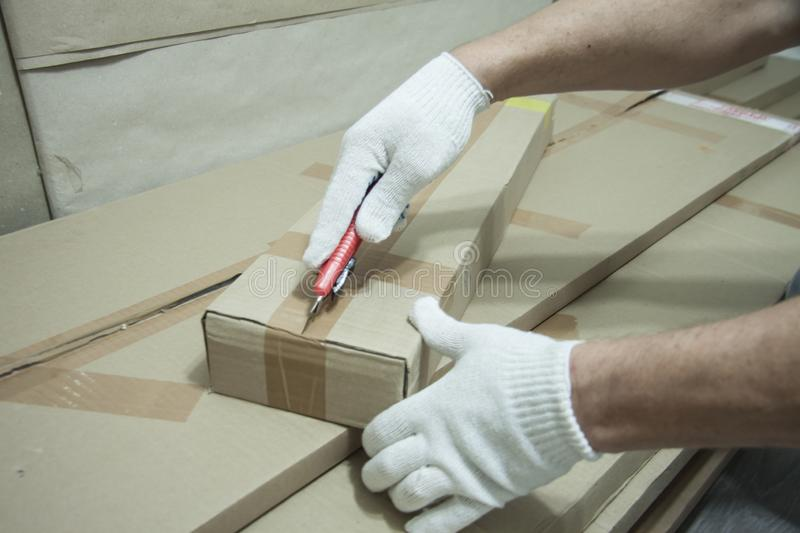 Male hands in white gloves with a knife unpack the box. Receiving mailings. Order from the store. Preparation for repair work indoors stock photos