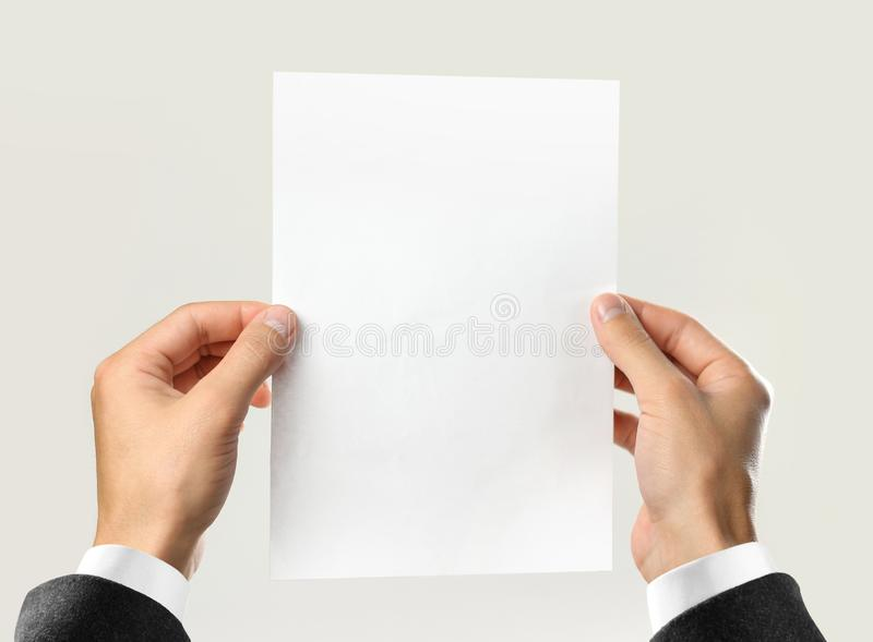 Male hands in white shirt and black jacket holding a white sheet of paper. Isolated on gray background. Closeup.  royalty free stock image