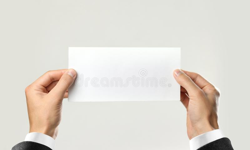 Male hands in white shirt and black jacket holding a white sheet of paper. Isolated on gray background. Closeup.  royalty free stock photo