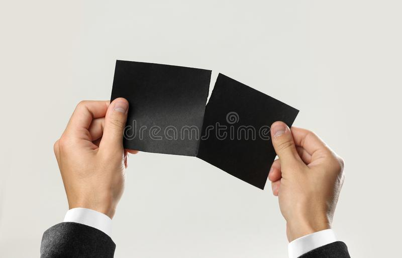 Male hands in white shirt and black jacket rip a black sheet of paper. Isolated on gray background. Closeup.  stock images