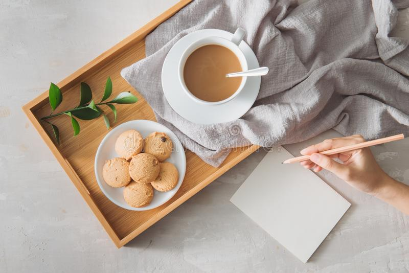 Male hands writing post card on the stone table with cup of coffee and cookie. Business with love concept royalty free stock photo