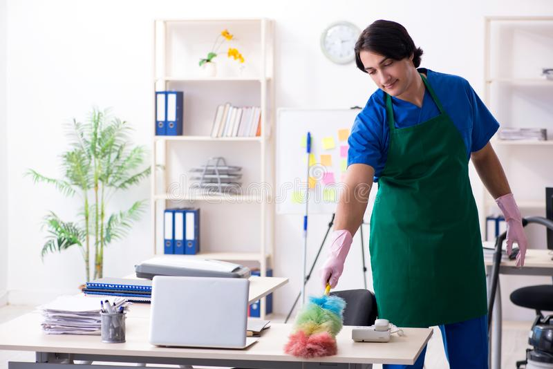 Male handsome professional cleaner working in the office royalty free stock photography