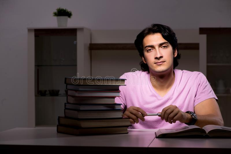The male handsome student preparing for exams late at home. Male handsome student preparing for exams late at home stock photos