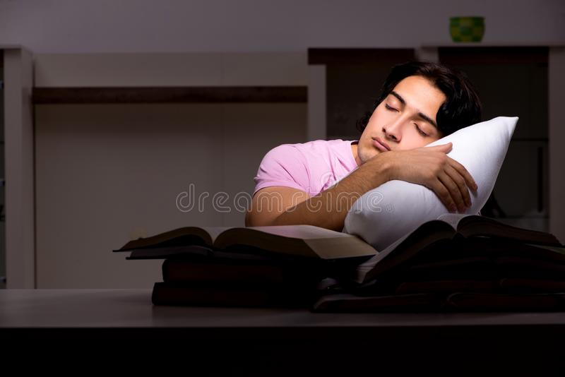 The male handsome student preparing for exams late at home. Male handsome student preparing for exams late at home royalty free stock photography