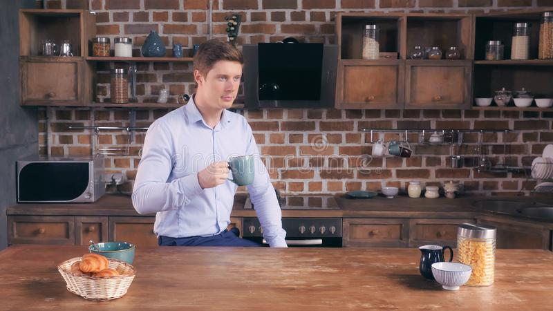 Male has unhealthy breakfast in flat. Focused young man drinking coffee sitting in the kitchen at home. Caucasian businessman relish drink before hard day. Guy stock photos