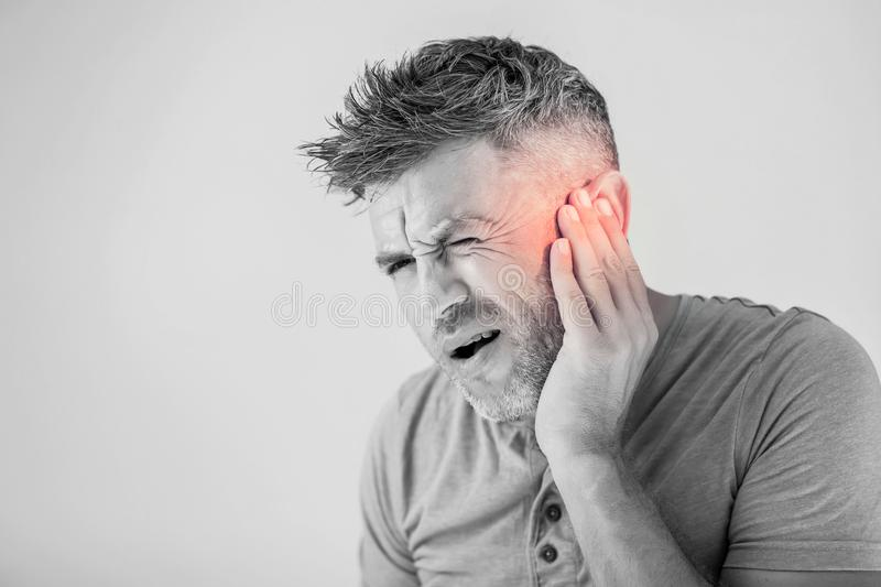 Male having ear pain touching his painful head isolated on gray. Background stock images
