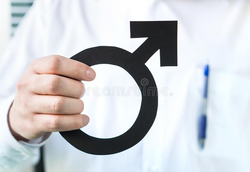 Male health concept. Doctor holding man symbol. Specialist or urologist royalty free stock images