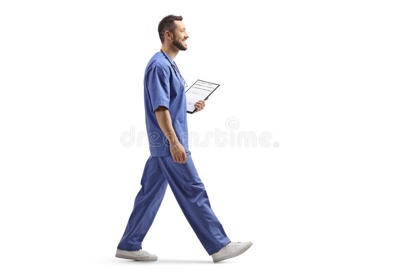 Male health worker in a blue uniform walking and holding a clipboard stock photo