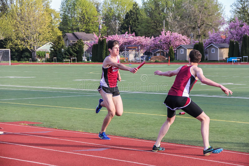 Male High school athletes pass the baton in the 4 x 400 relay in a track meet. Corvallis, Oregon, April 6, 2016: Male high school teammates pass the baton in the stock image