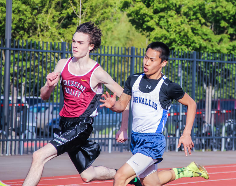 Male High school athletes run 200 meter race in track meet. Corvallis, Oregon, April 6, 2016: Cross town rival high school athletes run 200-meter race at track stock photography