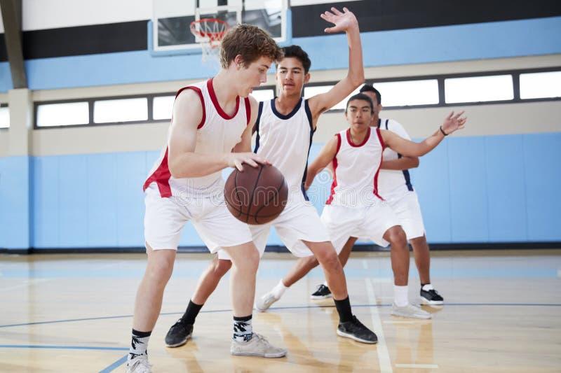 Male High School Basketball Team Dribbling Ball On Court stock photos