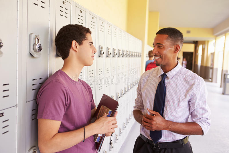 Male High School Student Talking To Teacher By Lockers. Smiling At Each Other stock image