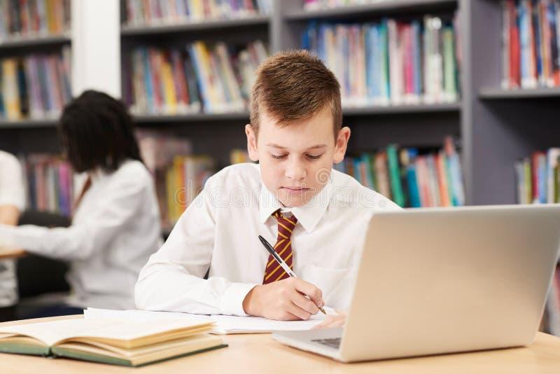 Male High School Student Wearing Uniform Working At Laptop In Li stock photo