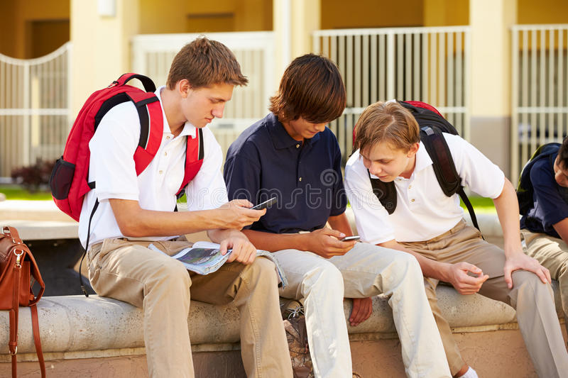 Male High School Students Using Mobile Phones On School Campus. Sitting Outside stock images