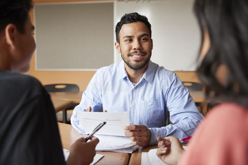 Male High School Tutor With Two Students At Desk In Seminar stock image