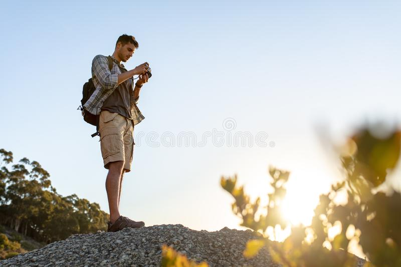 Male hiker with camera on hill top stock images
