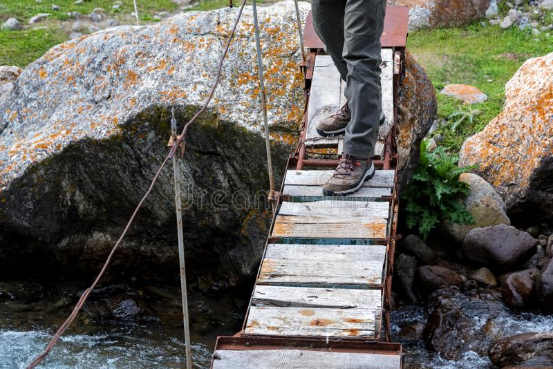 Legs of hiker on narrow wooden bridge over mountain river stock photo