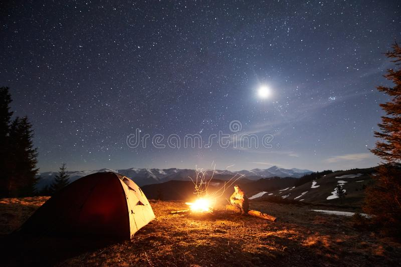 Male hiker have a rest in his camp near the forest at night under beautiful night sky full of stars and the moon. Male hiker have a rest in his camp near the stock image