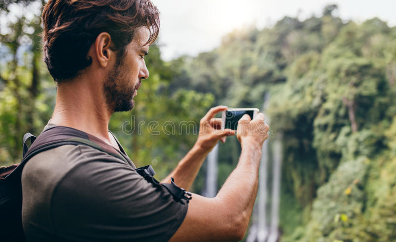 Male hiker photographing a water fall in forest stock images