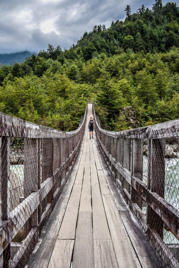 A male hiker on a wooden bridge over a river in Chile. stock photos
