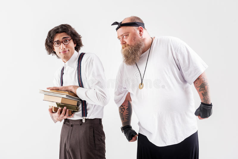 Male hipster is asking for help in young outcast. Give me write off. Large fat men is standing and staring at smart boy with eyeglasses with request. Thin stock photo