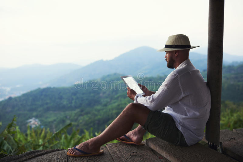 Male is holding portable digital tablet while connecting to internet in mountains setting. Young man wanderer is reading electronic book on touch pad, while is royalty free stock photography