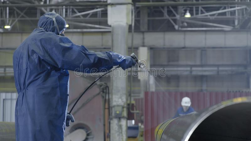 Male holding spray gun and painted steel. Man paints pipe atomizer royalty free stock photography