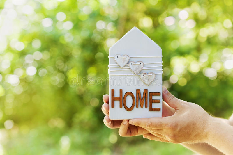 Male holds in hands house decorated hearts on green bokeh background. Real estate, buying a new home, insurance, sun energy, eco. stock photos