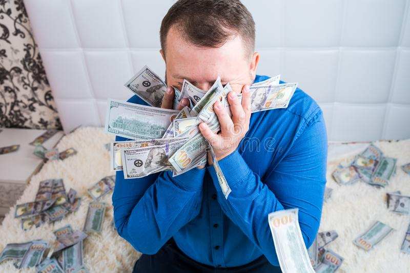Male holds in his hands a lot of money. and kisses them. A man enjoys a lot of cash dollars. Tremendous wealth concept. stock image