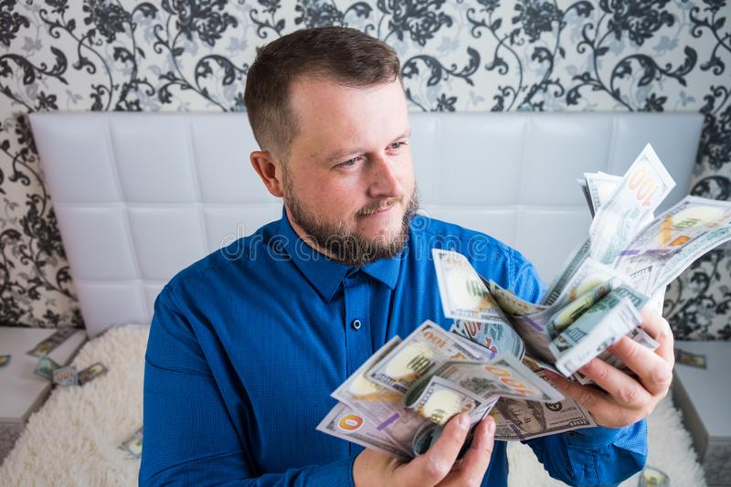 Male holds in his hands a lot of money. A man enjoys a lot of cash dollars. Tremendous wealth concept stock photo