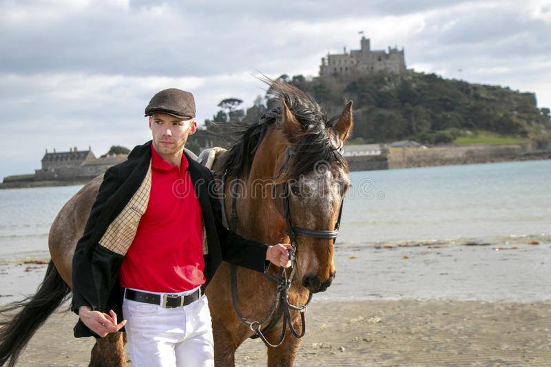 Handsome man, Male Horse Rider walking with his horse on beach, wearing traditional flat cap, white trousers, red polo shirt stock photos