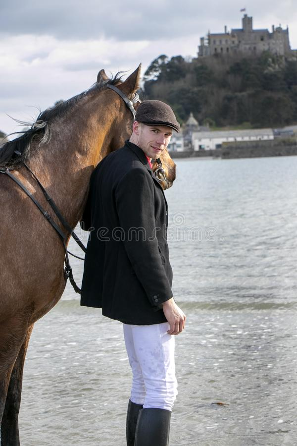 Handsome man, Male Horse Rider walking with his horse on beach, wearing traditional flat cap, white trousers, red polo shirt royalty free stock image