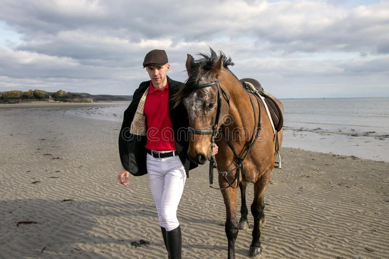 Handsome man, Male Horse Rider walking with his horse on beach, wearing traditional flat cap, white trousers, red polo shirt stock image