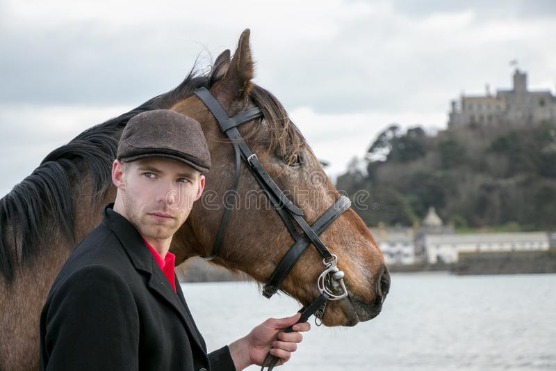 Handsome man, Male Horse Rider walking with his horse on beach, wearing traditional flat cap, white trousers, red polo shirt stock images