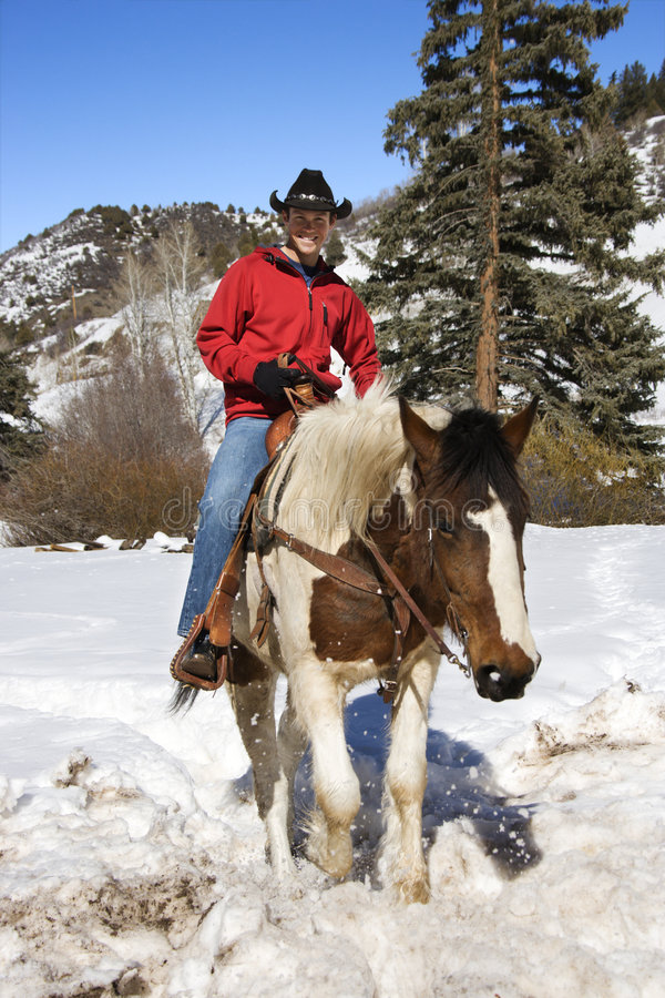 Male horseback riding. MId-adult Caucasian male horseback riding looking at viewer royalty free stock photography